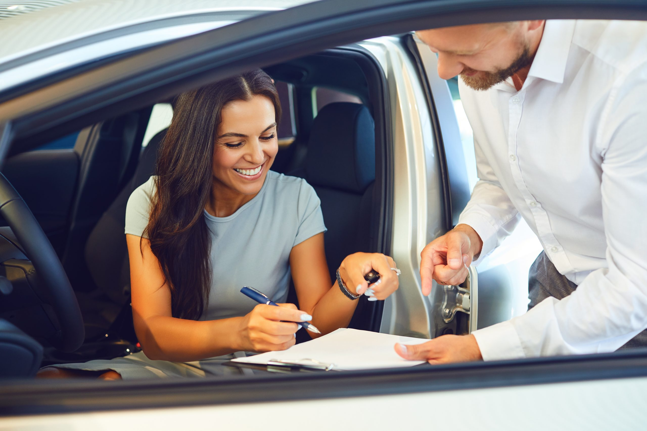 A young woman buys a car in a car showroom. A man signs a car agreement.